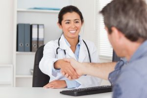 pretty female doctor shaking a patient's hands in her office
